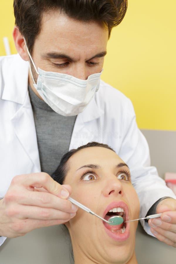 画像年轻美女害怕牙医工具 免版税图库摄影