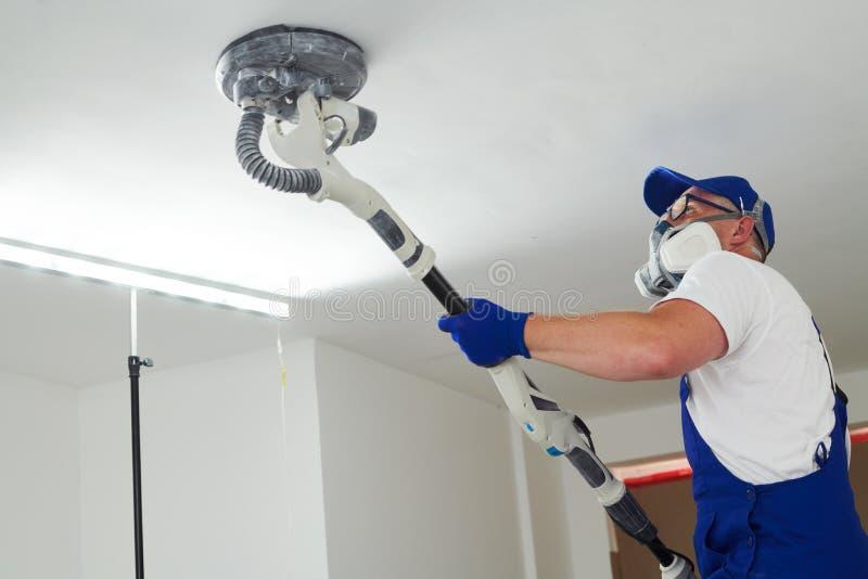 画家与天花板一起使用 擦亮和铺沙表面在绘的油灰以后 免版税库存照片