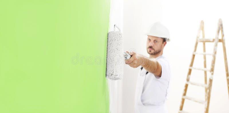 画家人在与漆滚筒一起使用,壁画绿色col 免版税库存图片