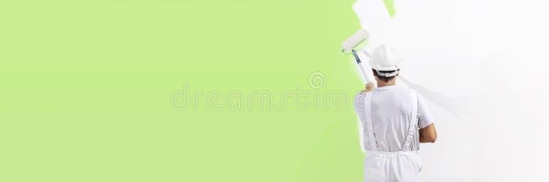 画家人在与漆滚筒一起使用,壁画绿色col 免版税库存照片