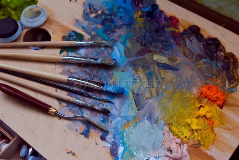 画家的刷子,弄脏用不同的油漆和一句paletteknife谎言在木调色板有混杂的明亮的油漆混乱的  免版税图库摄影