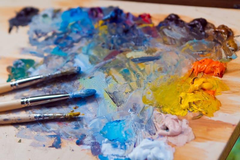 画家的刷子,弄脏用不同的油漆,在木调色板的谎言有新拌合的明亮的油漆混乱的  库存照片