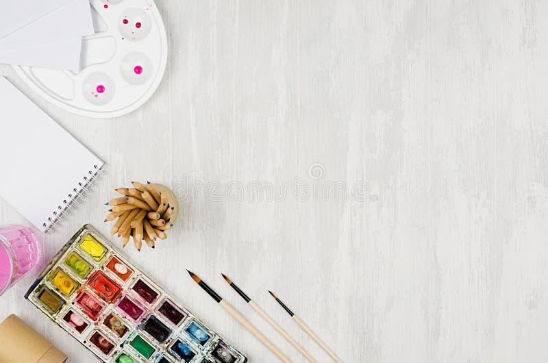 画家的文具-油漆,调色板,刷子,上色了铅笔,在白色木背景,顶视图,拷贝空间的写生簿 免版税库存照片