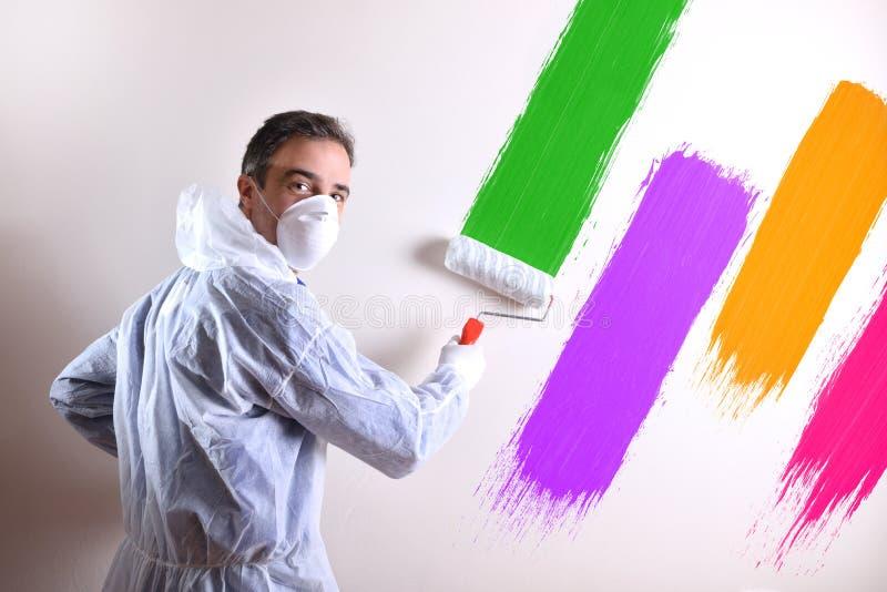 画家转动与overals的和墙壁绘了与四种颜色 免版税库存图片