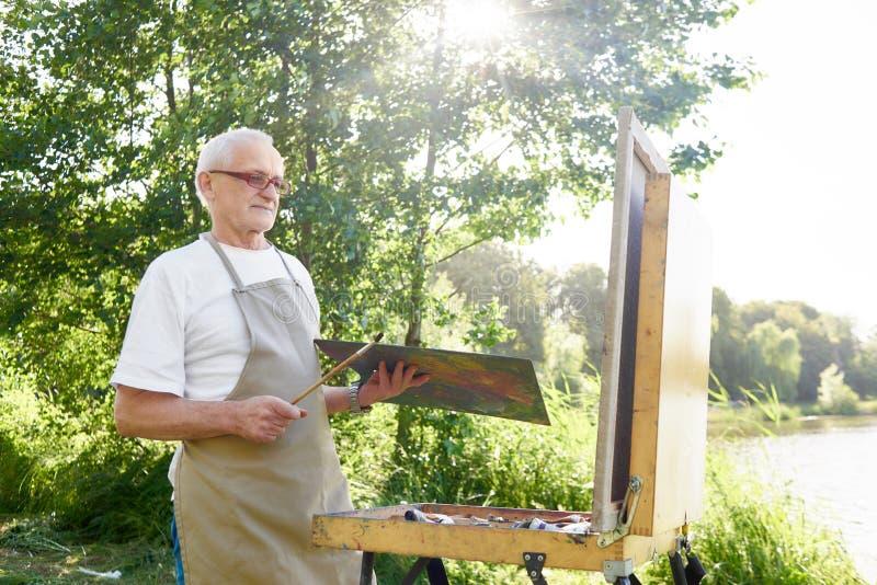 画家,站立在公园和拾起油漆生动描述 免版税库存照片