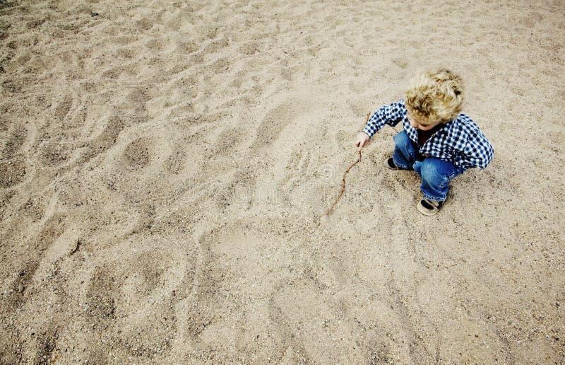 画少许沙子的男孩 免版税库存照片