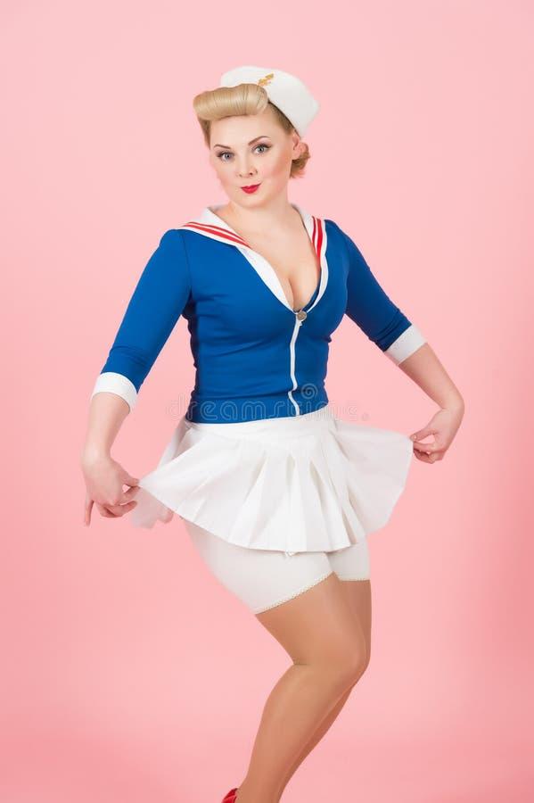 画报样式的水手女孩与白色裙子 芳香树脂称呼了桃红色的白肤金发的妇女 图库摄影