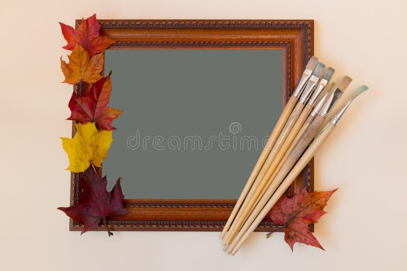 画框、画笔和五颜六色的秋叶 库存图片