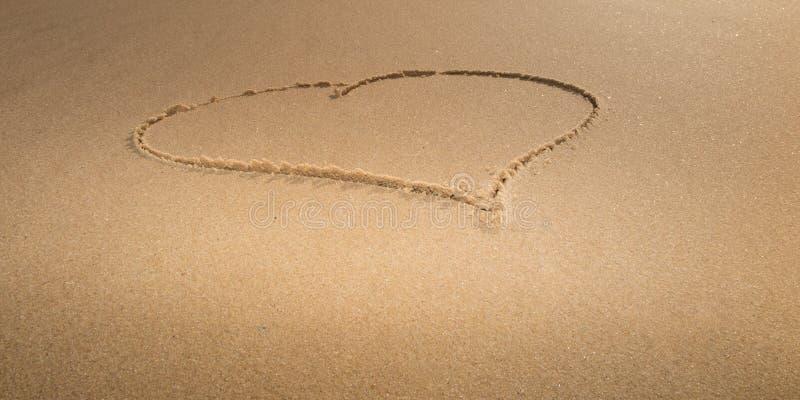 画爱心脏作为在黄沙的标志海上 库存照片
