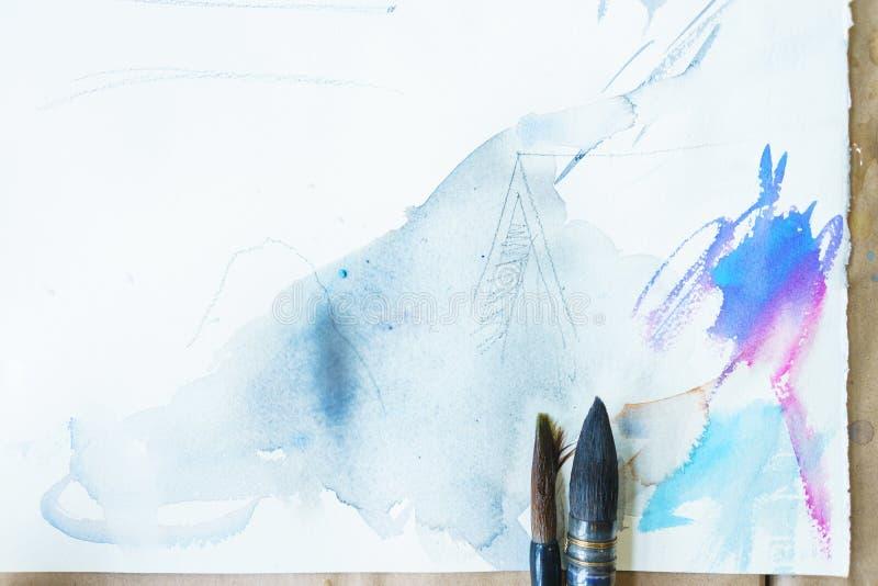 画的水彩 白皮书、帆布、刷子和美丽的油漆污点顶视图 免版税图库摄影