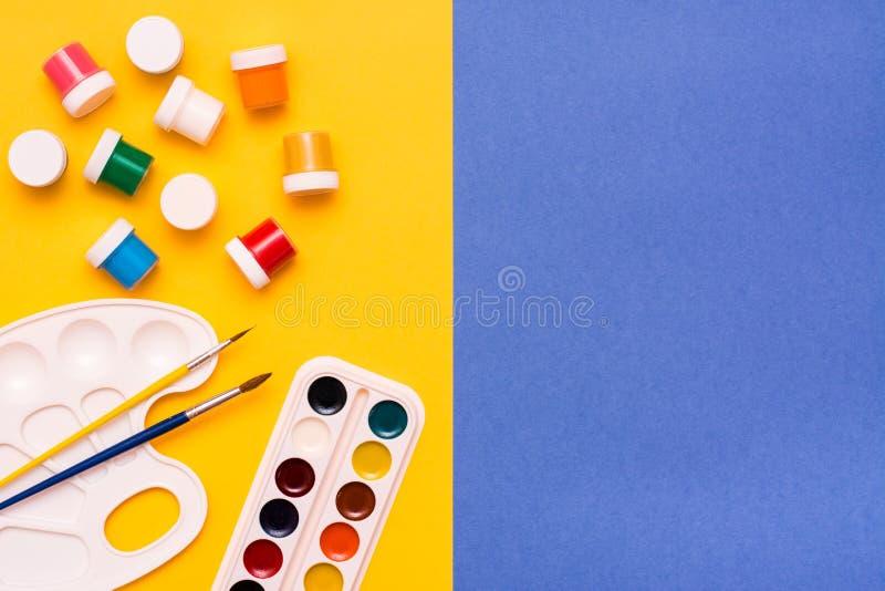 画的辅助部件-水彩、树胶水彩画颜料和刷子 免版税库存照片