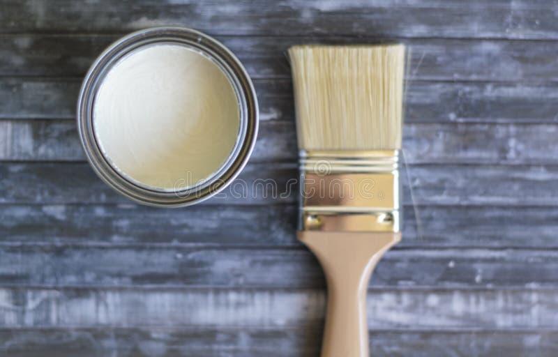 画笔和罐头顶视图在蓝色背景的白色油漆 免版税库存图片
