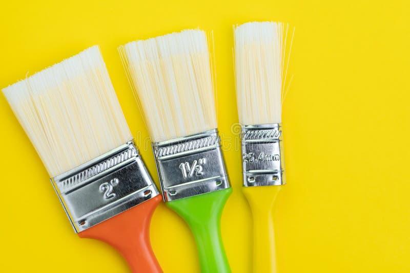 画笔的五颜六色的各种各样的大小在坚实黄色背景的与拷贝空间使用作为艺术、色板显示或者设计观念 库存照片