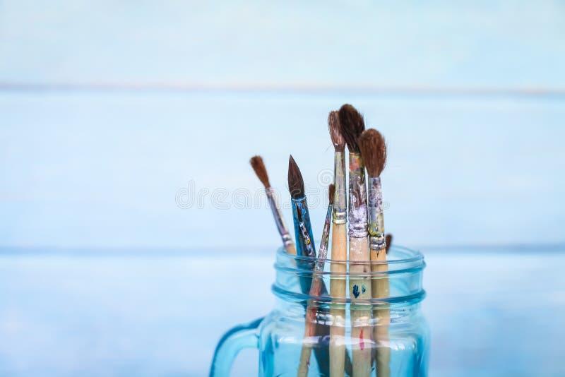 画笔的关闭在木蓝色难看的东西背景的玻璃瓶子站立 免版税库存照片