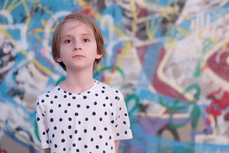 画象一个孩子对有街道画的墙壁 免版税库存照片