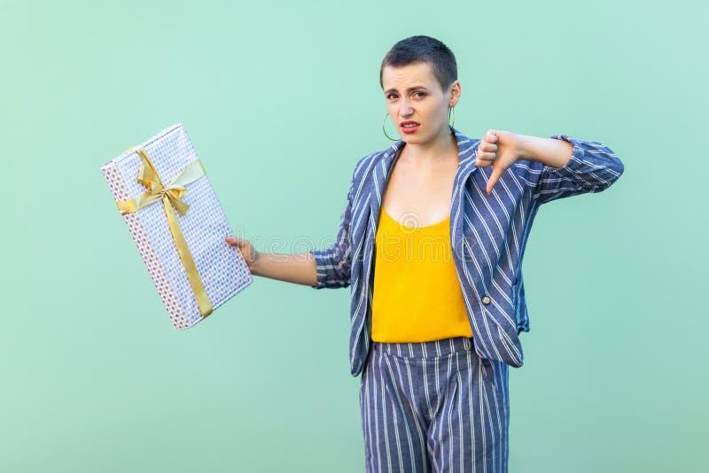 画象不满意与镶边衣服身分的短发年轻女人,显示反感姿态到她的当前箱子,看 免版税库存照片