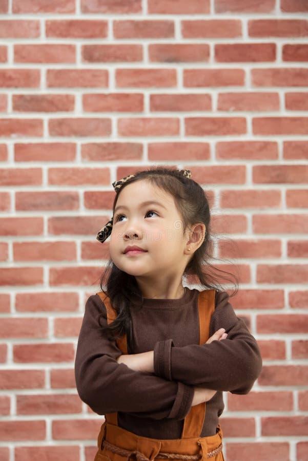 画象与胳膊的女孩身分横渡在砖墙 免版税库存照片