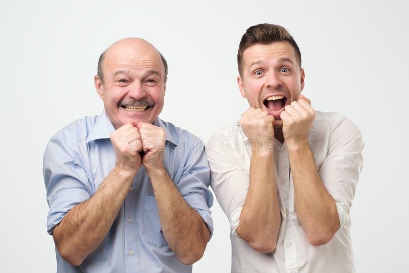 画象两个惊奇的人看与嘴的父亲和儿子或者最好的朋友照相机开放 免版税库存照片