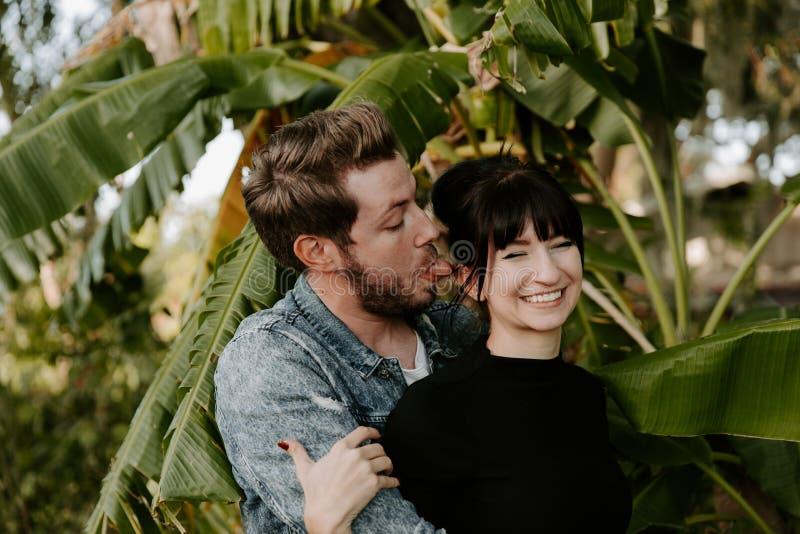 画象两个逗人喜爱的现代白种人美丽的年轻人成人人男朋友夫人Girlfriend在爱的Couple Hugging和亲吻在Na 免版税库存照片