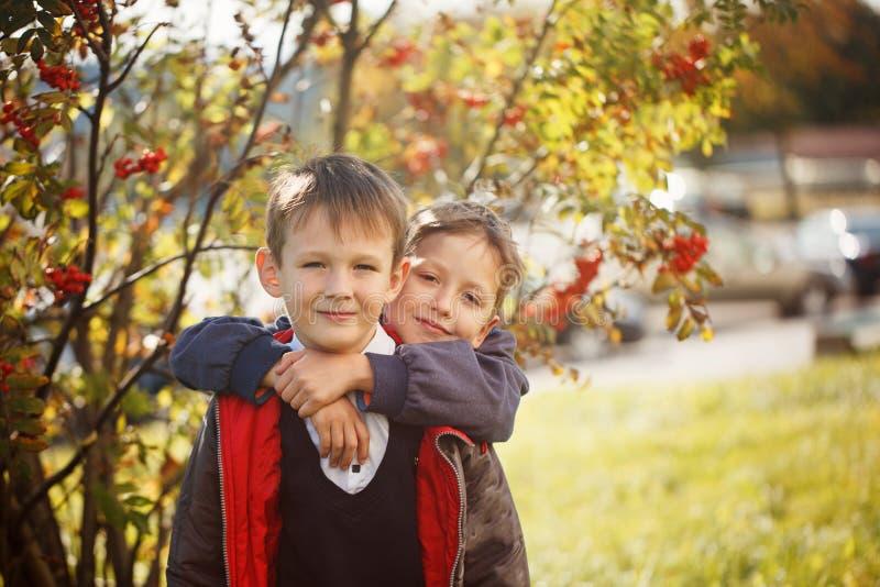 画象两男孩、兄弟和最好的朋友微笑 朋友拥抱 免版税库存照片