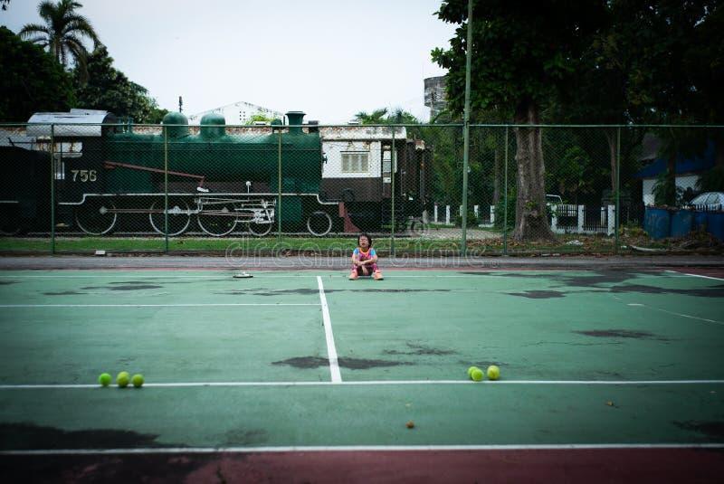 画象亚裔女孩坐网球场在艰苦使用以后 图库摄影