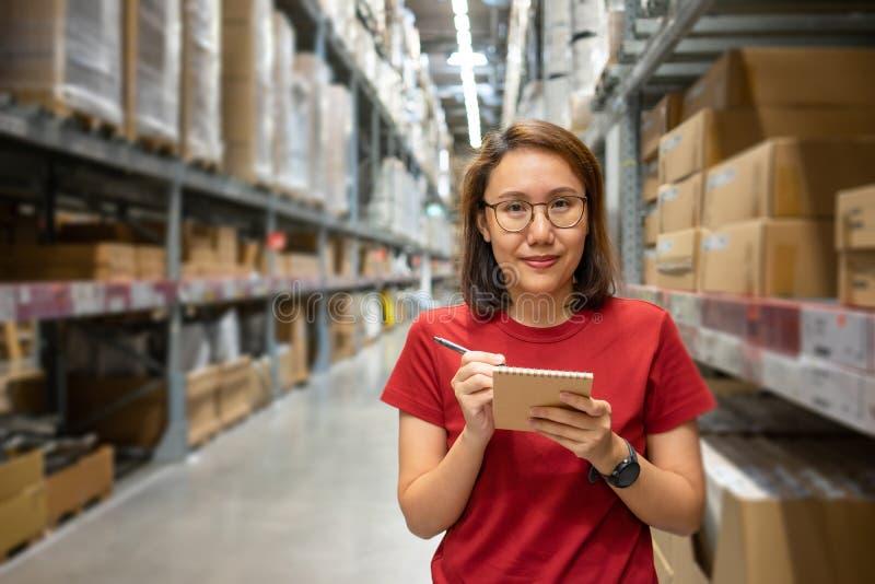 画象亚裔妇女,职员,计数仓库控制经理的产品站立,计数和检查在的产品 免版税库存图片