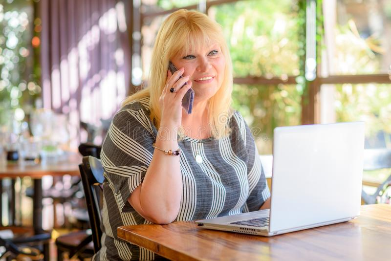 画象典雅的中部变老加上谈话在电话和研究在创造性的办公室或咖啡馆的膝上型计算机的大小女实业家 免版税库存图片