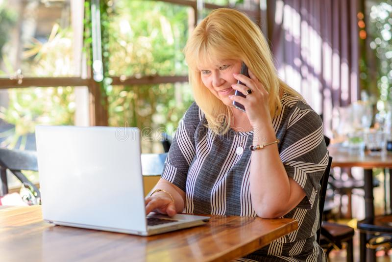 画象典雅的中部变老加上谈话在电话和研究在创造性的办公室或咖啡馆的膝上型计算机的大小女实业家 库存照片