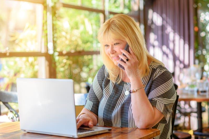 画象典雅的中部变老加上谈话在电话和研究在创造性的办公室或咖啡馆的膝上型计算机的大小女实业家 库存图片