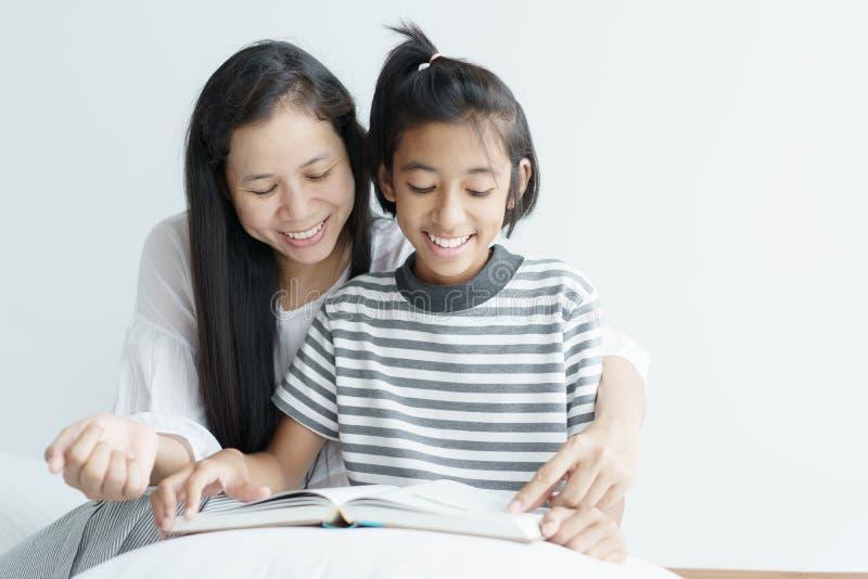 画象图片爱家庭母亲和女儿坐的看书 逗人喜爱的女孩微笑美好和愉快在床上 免版税图库摄影