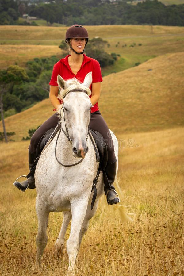画象在一件红色球衣打扮的被射击一美丽的愉快的微笑的年轻女人骑她的白马通过长 库存照片