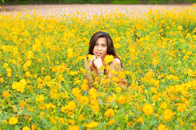 画象妇女和黄色花或者波斯菊sulphureus贾夫 免版税库存图片