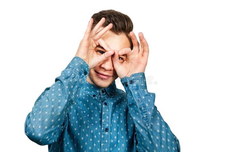 画象年轻人身穿蓝服衬衣 人打开他眼睛宽手手指微笑 查出的空白背景 免版税库存照片