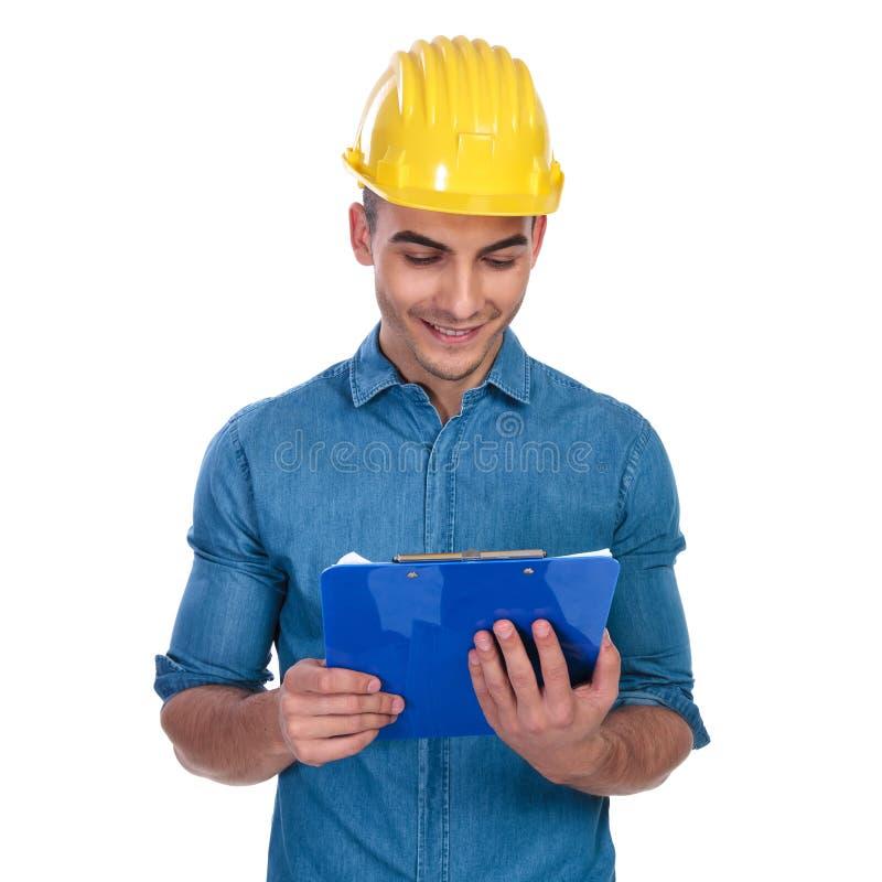 画象年轻工程师藏品剪贴板和读 免版税库存照片
