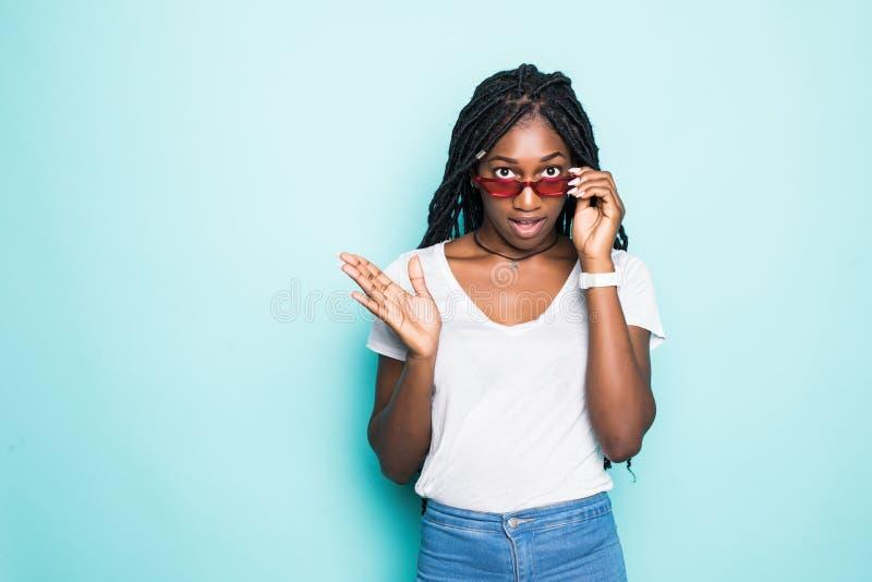 画象年轻非洲妇女微笑的看在现代太阳镜的照相机被隔绝在蓝色背景 免版税库存图片