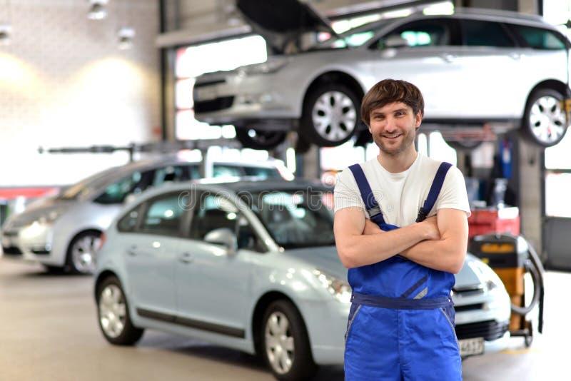 画象微笑的汽车修理师在车间-与在Th的特写镜头 免版税库存图片