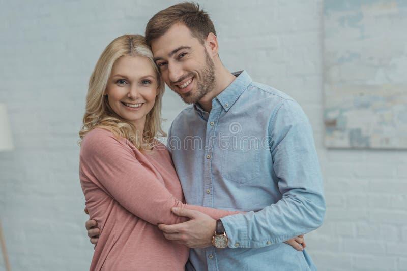画象愉快的母亲和增长的儿子拥抱 图库摄影