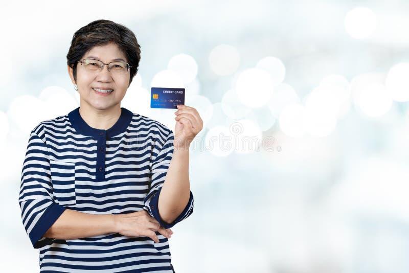 画象愉快的资深亚洲妇女举行信用卡和在手边显示 库存照片