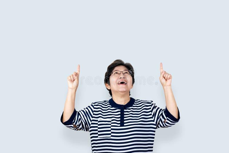 画象愉快的资深亚洲妇女姿态或指向手和手指和看上面 免版税库存照片