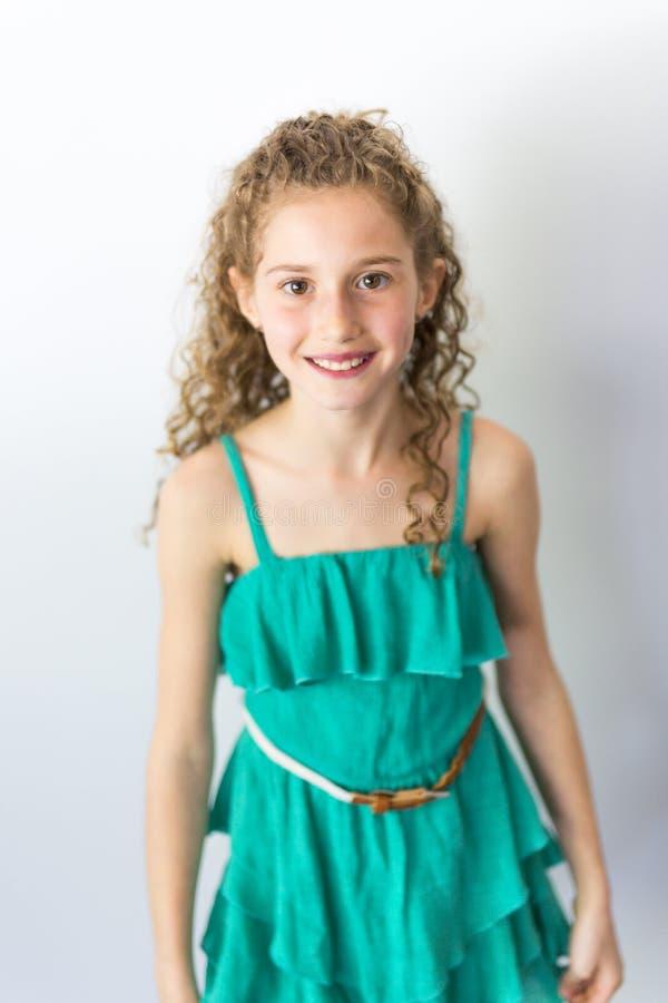 画象愉快,微笑,确信的9岁有卷发的女孩,隔绝在灰色 免版税图库摄影