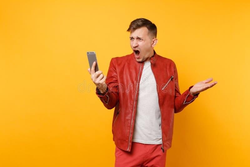 画象时髦尖叫红色皮夹克T恤杉的恼怒的秋天年轻人使用在明亮趋向隔绝的手机 免版税库存照片