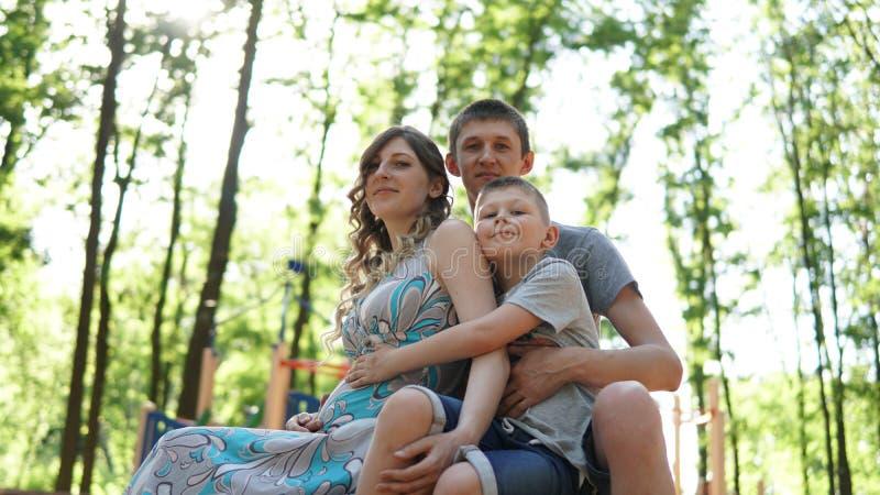 画象有儿子的年轻父母在夏天公园 妈妈、爸爸和孩子 图库摄影
