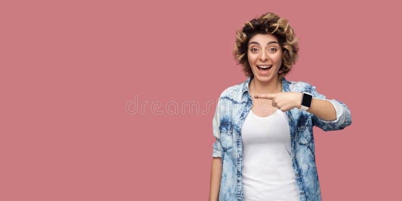 画象有卷曲发型的惊奇年轻女人在偶然蓝色衬衣身分和指向背景空的copyspace与 免版税图库摄影
