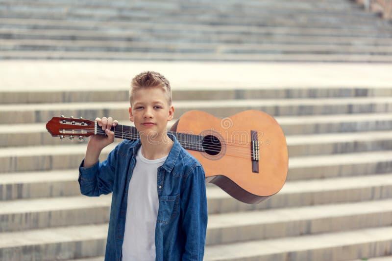 画象有声学吉他的少年男孩在公园 库存照片