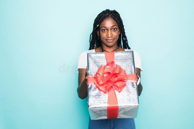 画象有非洲的发型藏品礼物盒的欢悦非洲妇女和微笑在蓝色背景的幸福 免版税库存照片