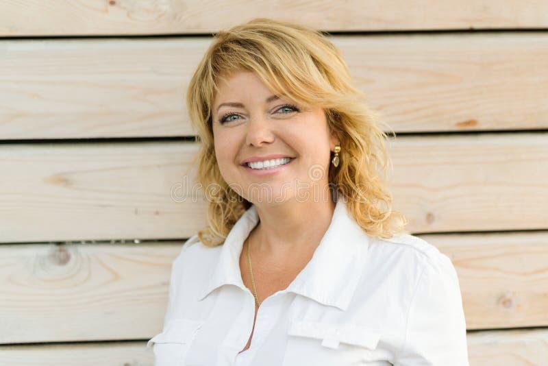 画象正面成熟中年妇女微笑的特写镜头 白肤金发的妇女,室外木背景 库存照片