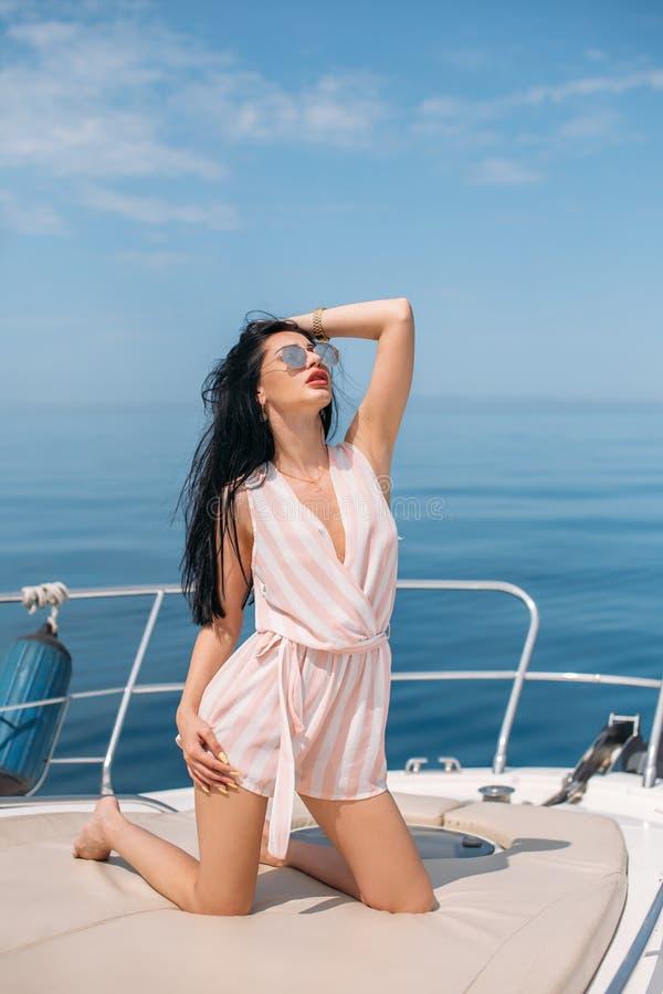 画象深色女性摆在帆船的海海洋背景 库存照片