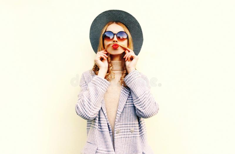 画象滑稽的妇女显示髭她的吹红色嘴唇的头发获得乐趣在圆的帽子 库存图片