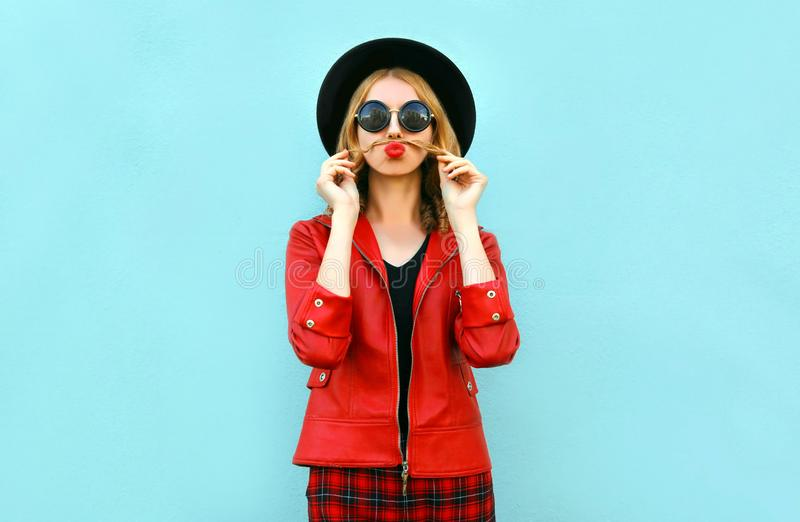 画象滑稽的妇女陈列髭她的吹红色嘴唇的头发获得乐趣在黑圆的帽子,在蓝色的红色夹克 图库摄影