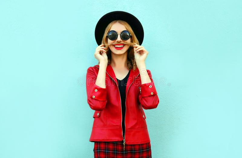 画象滑稽的微笑的妇女陈列髭她的在黑圆的帽子,在蓝色的红色夹克的头发 免版税库存照片
